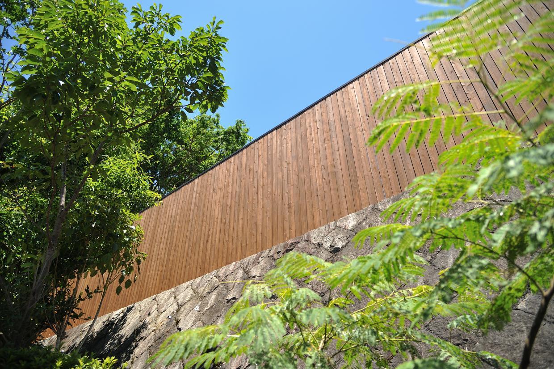露天風呂側から見上げる木の塀。青空や木々の緑と調和しています。